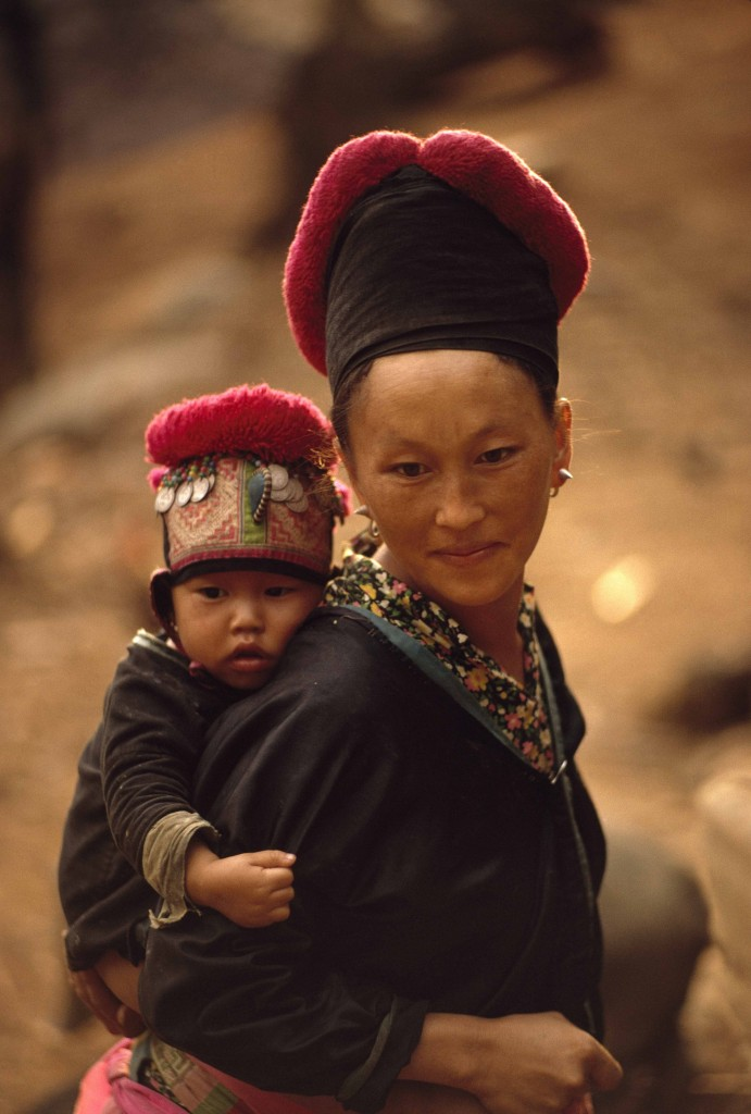 W.E. GARRETT, Una donna hmong e suo figlio con il copricapo tradizionale. Laos 1974